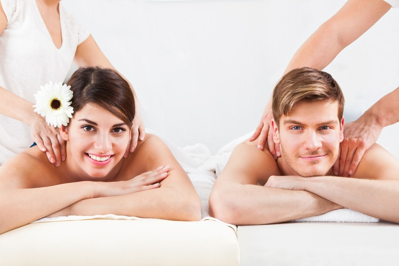 Portrait of smiling young couple receiving massage at spa